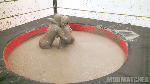 two mud covered girls in a battle of strength