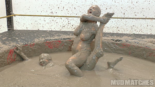 Shauna reaches from the mud for help as Kym locks her leg.